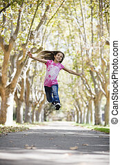 Tween Girl Jumping - Portrait of Smiling Tween Girl Jumping...