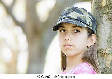 Portrait of Tween Girl In Cap Standing Against Tree