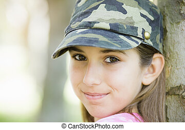 Portrait of Smiling Tween Girl Leaning Against Tree