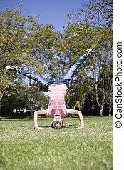Tween Girl doing Headstand - Portrait of Smiling Tween Girl...
