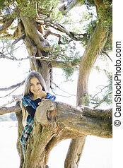 Portrait of Smiling Tween Girl Standing in a Tree