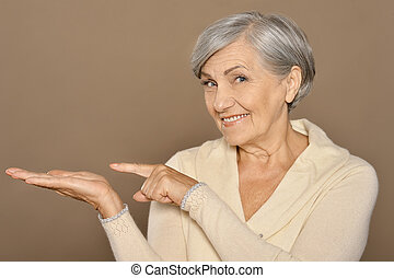 Senior woman pointing - Portrait of senior woman pointing by...