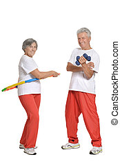 Portrait Of A Senior Couple Exercising With Dumbbells and...