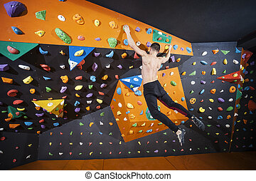 Man practicing bouldering in indoor climbing gym - Young man...