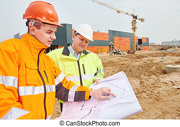 builder workers at construction site - two engineers...