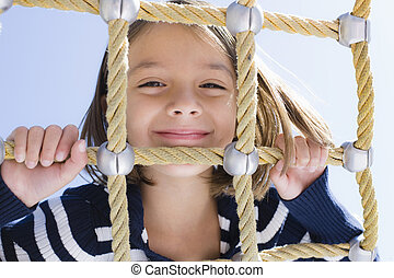 Girl On Hammock - Young Girl Lying on Stomach Looking...
