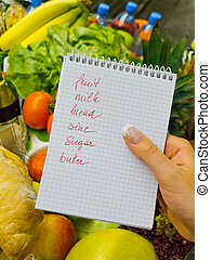 shopping list in the supermarket - a woman holding a...