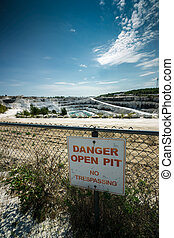 Danger Open Pit Sign - A sign reading Danger Open Pit hangs...