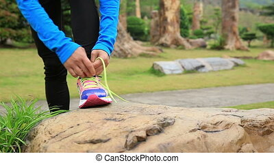 tying shoelace - young asian woman runner running and tying...