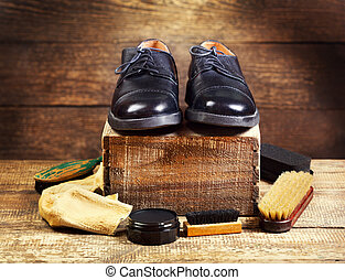 black shoes with care accessories on a wooden background