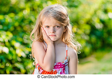 Sad little girl with long blond hair suffering from...