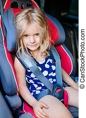 Adorable smiling little girl with long blond hair buckled in...