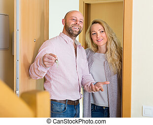 Couple coming to see new flat - Happy smiling married couple...