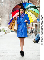 woman in blue with shopping bags and umbrella  at  street