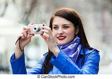 Happy girl with digital camera taking a photo