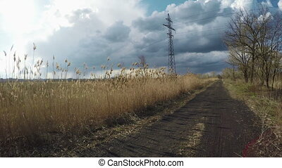 Road near power lines - Driving on road with reeds pole by...