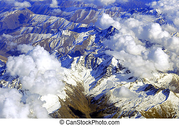 Aerial view of mountains from airplane, clouds, sky