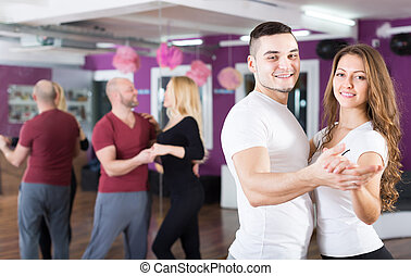 Group dancing in club - Group of smiling young adults...