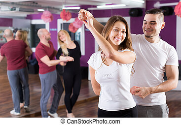 Couples having dancing class - Two young smiling couples...