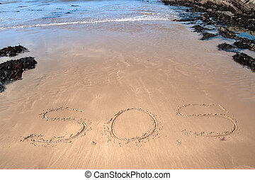 sos - s o s inscribed on the beach with waves in the...