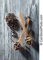 Nutmeg, clove and allspice in old spoon on wooden table -...