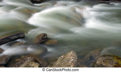 Close up abstract view of rushing water flowing down the...