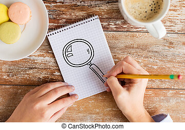 close up of hands drawing magnifier in notebook - business,...
