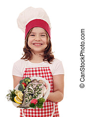 happy little girl cook with prepared trouts on plate