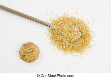 Brown sugar on silver teaspoon with cookie arranged on white...