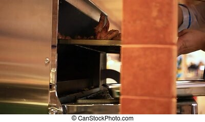 Chef putting meat into oven in the kitchen