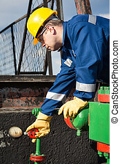 Worker on the oil field. Refinery, oil and gas