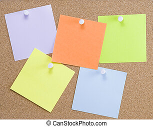 Colorful sticky notes attached to a corkboard with white...