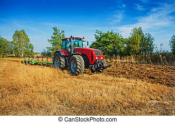 agricultural processing tractor plowing field in spring...