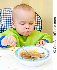 Baby eating - Little baby girl eating with spoon in a...