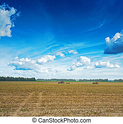 tractors processing field after harvesting agricultural...