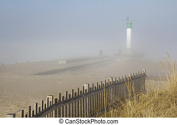 Two people walking on a lighthouse pier on a misty morning