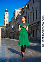 Woman traveling in Dubrovnik city - Young woman in green...