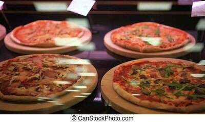 different types of pizzas on display for sale at the grocery...