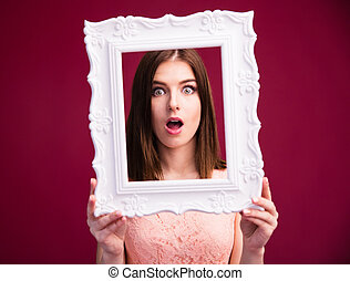 Surprised woman looking at camera through frame over pink...