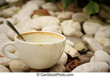 coffee cup wih tea spoon on stone background.