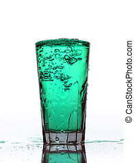 Glass of splashing Turquoise lemonade isolated on white...