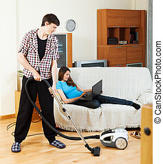 Man cleaning with cleaner during woman over sofa - Man...