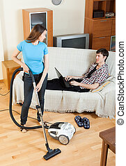 woman doing house cleaning during man resting - woman doing...