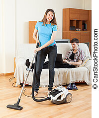 woman doing house cleaning with vaccuum cleaner - Young...