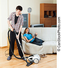 Man cleaning while woman lying with laptop - Man cleaning...