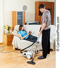 man cleaning while girl lying with eBook - Young man...