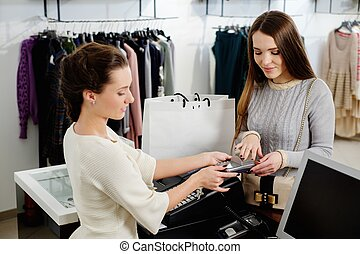 Happy woman customer paying with credit card in fashion...
