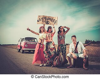 Multinational hippie hitchhikers with guitar and luggage on...