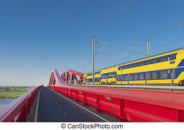 red railroad bridge - train passing the new red railroad...