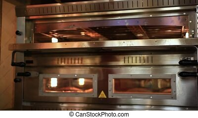 Chef puts dough in the oven for pizzas and close Oven,...